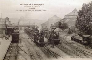 La gare, les voies de chemin de fer, les deux rotondes et les locomotives à vapeur.